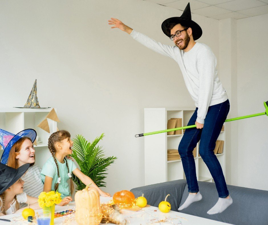 man flying on broom for halloween with children laughing