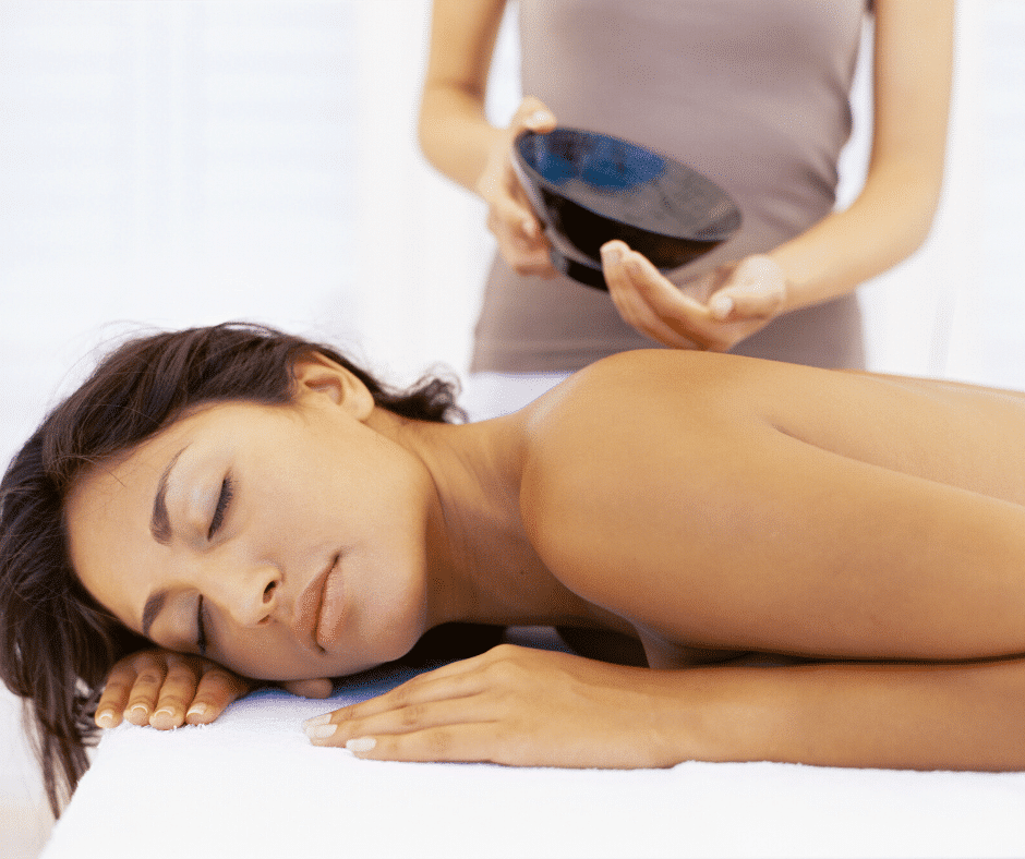Woman on massage table with massage therapist