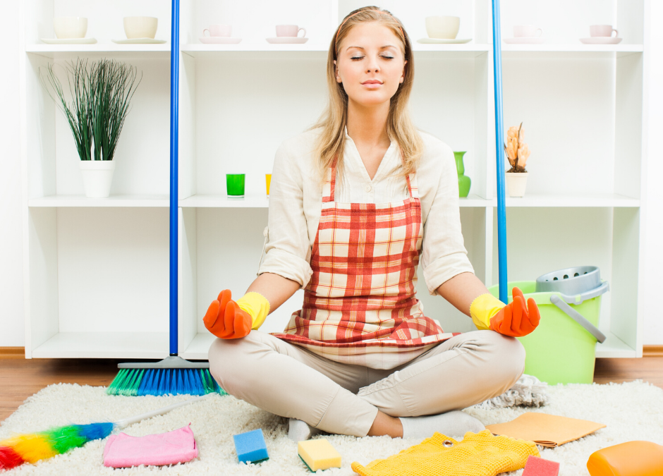 woman meditating among her cleaning supplies
